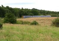A 4-car DMU on a Tweedbank – Edinburgh service about to pass below the bridge carrying the B704 road as it approaches the Newtongrange stop on 9 July 2017. The photograph was taken from the roadside 100m west of the bridge. The wood in the background  stands on the site of the loading area and sidings that once served Lady Victoria Pit. [See image 6116] [Ref query 1096]<br><br>[John Furnevel&nbsp;09/07/2017]