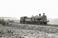 An ex-Caledonian 0-6-0 approaching Dykes Junction, Ayrshire, propelling a brake van on 30 March 1959. The guard appears to be making advance preparations for the next manoeuvre. [Ref query 1650]<br><br>[G H Robin collection by courtesy of the Mitchell Library, Glasgow&nbsp;30/03/1959]