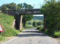 The Esk Valley line to Whitby crosses the River Esk and the local road to Lealholm in rapid succession shortly after leaving Danby Station heading east. The view looking south shows the second bridge, the road bridge, which, for a rural location, has a motorway headroom of 16 feet. The section of the bridge on the far side has a higher still headroom, having been rebuilt in the recent past. The river bridge is some 25m to the right.<br><br>[David Pesterfield&nbsp;18/06/2017]