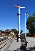 The Station Master (Stinsen) sets the signal on the platform at Hesselby to <I> line clear </I>. This heritage narrow gauge railway recreates some of the aspects of railway operation on the Swedish Baltic island. Gotland had several 891mm gauge (3 Swedish feet) lines which first opened at the end of the nineteenth century/early twentieth century. Those that remained in operation were taken over by SJ in the 1940s but all were subsequently closed by 1960.<br><br>[Charlie Niven&nbsp;05/07/2017]