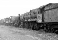 A very sad looking GWR 6023 <I>King Edward II</I>, in Barry scrapyard in 1975 with its rear driving wheels cut through. Beyond lie an equally decrepit GWR 2-8-0 and a Bulleid Light Pacific. At the time the painted <I>Reserved</I> notices on the King seemed optimistic but the Great Western Society has done a magnificent job of restoration [See image 58065].<br><br>[Mark Bartlett&nbsp;28/10/1975]