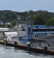 View from the stern of the ferry to the Isle of Gotland leaving Nynäshamn quayside. The two platform railway station is visible in the middle of the shot just to the left of the blue building. The station is about 400 hundred metres away from the ferry terminal and was served by local commuter trains to/from Stockholm Central Station. After the new underground route through central Stockholm, Citybanan, opened on 10th July the trains on this single track route now go to/from Stockholm City Station.<br><br>[Charlie Niven&nbsp;01/07/2017]