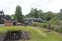 334024 passing the site of Sunnyside Junction signal box in July 2017, with the track into Gunnie Yard still visible. To the left is the entrance to the mock drift mine at Summerlee Heritage Park and also visible alongside the main line are NCB No.9 and two other preserved industrial locomotives. <br> <br><br>[Alastair McLellan&nbsp;12/07/2017]