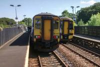 An Edinburgh-bound 156 and a 158 for Glasgow pass at Livi South on a fine 24 July.<br><br>[David Panton&nbsp;24/07/2017]