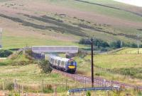 An Edinburgh bound train on the Borders Railway passes below a farm bridge just north of Heriot on the approach to Falahill. The train has approximately 5 miles to run to its next scheduled stop at Gorebridge.<br><br>[John Furnevel&nbsp;30/07/2017]