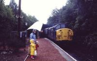 Passengers wait to catch the morning service from Glasgow to Oban service at Helensburgh Upper on a wet summers day in August 1985.<br><br>[John McIntyre&nbsp;/08/1985]