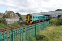 158818 leaves Llandudno heading for the Junction on 26th July 2017. The new bridge in an old style has recently replaced one of similar design, which many years ago replaced a level crossing at this point. The old crossing keeper's cottage seen here is still lived in.   <br><br>[Mark Bartlett&nbsp;26/07/2017]