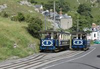 <I>Halfway to Halfway</I>. Trams 4 & 5 pass at the lower section loop of the Great Orme Tramway on 26th July 2017. Above this point the tracks are interlaced but below here there is just a single track dropping down a 1:4 gradient to Victoria station. Cars on the lower (street running) section have protective valances rather than an open chassis. The descending car moves the trailing point blade so that it takes the correct line coming back up again and wires don't get crossed!<br><br>[Mark Bartlett&nbsp;26/07/2017]