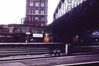 Out on the country end of Paddington station 08944 carries out some shunting in front of the signalbox while 31401 waits under Bishop's Bridge Road to take empty stock west to the carriage sidings.<br><br>[John McIntyre&nbsp;/08/1985]