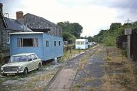 A peculiar queue of abandoned caravans and cars stretches along the track bed of the former Taunton-Barnstaple line at Bishops Nympton and Molland station on 11th September 1976. It was as if holiday motorists had tried to use the disused railway as an alternative to the congested roads and come to grief. Substantial holiday traffic had indeed come this way in the past, but on rails until the line closed in 1966. [Ref query 1125]<br><br>[Mark Dufton&nbsp;11/09/1976]