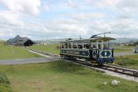 A descending Great Orme tramcar nearing the winding house at Halfway on 26th July 2017. Because the cars on the upper level are hauled from Halfway they are fastened to a continuous loop cable rather than just <I>hanging</I> from it as on the lower section. They also operate on a reserved track and so don't need protective side guards.<br><br>[Mark Bartlett&nbsp;26/07/2017]