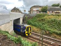 A slightly delayed Edinburgh - Glasgow service passes under the new Station Road overbridge opened to traffic a few days previously. Some landscaping and tidying work remains to be done on the east side, while on the station side the platform 1 pedestrian steps and ramp have not yet reopened.<br><br>[Colin McDonald&nbsp;18/08/2017]