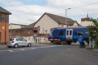 380111 crosses Princes Street on its way to Ardrossan Harbour. The crossing is protected with half barriers. On the left is a new building built on the site of the station building.<br><br>[Ewan Crawford&nbsp;10/08/2017]