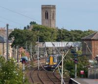 A Ardrossan Harbour bound 380108 approaches Ardrossan South Beach viewed through electrical clutter. The tower of St Cuthbert's Church looks on.<br><br>[Ewan Crawford&nbsp;10/08/2017]