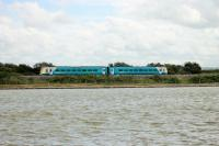 An Arriva Class 175 nears Rhyl station running along the embankment to the west of the station on 27th July 2017. The train is passing the Marine Lake and the Rhyl Miniature Railway runs between the lake and the embankment wall. [See image 60271]<br><br>[Mark Bartlett&nbsp;27/07/2017]