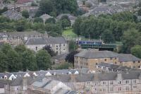 Seen across the Dumbarton rooftops, from the ramparts of the Castle, a Class 320 EMU pauses at the East station on its way to Balloch. 3rd August 2017. <br><br>[Mark Bartlett&nbsp;03/08/2017]