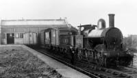 An ex-LNWR <I>Cauliflower</I> 0-6-0, LMS No. 8525, standing in Knott End station with a mixed goods train apparently ready to head back towards Garstang in a splendid but undated photograph. The glass fronted covered area for passengers between the buffers and main building can be seen but the platform is grass covered so the 1930 withdrawal of passenger services may have taken place. Later photos, but prior to the complete closure in 1950, show the covered area removed and just the brick station building visible. The loco is in a post 1928 livery but taken prior to the late 30s and early 40s renumbering of ex-LNWR locos, whereby this example would have become 28525. <br><br>[Knott End Collection&nbsp;//]