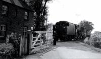 An unidentified LMS Black 5 crossing the minor road at Cogie Hill with a goods train returning from Pilling towards Garstang, probably sometime in the early 1960s. Between 1908 and the 1930 withdrawal of passenger services there was a small request halt here. The crossing keeper's cottage survived the 1963 closure of the line. [See image 18313] for a modern day comparison from the same spot.<br><br>[Knott End Collection&nbsp;//]