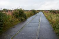 This was one of the lines serving the Nobel Explosives site at Ardeer. It was concreted over to provide road (and retain rail) access to the site from the north east, thus preserving the line.<br> <br> The branch originally served Misk Colliery No1, Bogend Pit and a chlorine works.<br> <br> The branch closed when severed by the A78 dual carriageway. Track on this section was, not surprisingly, left in place. This is the view east to Stobbs Junction with the A78 on the left.<br><br>[Ewan Crawford&nbsp;07/09/2017]