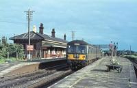 A Cravens DMU pulls away from Garstang and Catterall heading for Lancaster as alighting passengers head for the footbridge. Prior to 1930 there would have been a connection to the Knott End branch railmotor on the other side of the island platform. The main station building can be seen on the Up line. This splendid colour photo was probably taken in the late 1960s. The 1964 timetable shows four Up and five Down departures on weekdays with an extra mid-day service each way on Saturdays. The station closed in 1969, following which the site was cleared for the 1972 WCML electrification. <br><br>[Knott End Collection&nbsp;//]