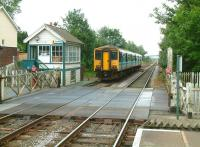 A DMU for Great Yarmouth leaves Cantley, Norfolk, on 19 July 2002. Platform view east over Station Road level crossing.  <br><br>[Ian Dinmore&nbsp;19/07/2002]