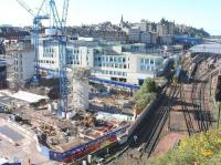 After many years of delays due to planning objections, design revisions, additional consultations, archaeological digs, a recession, etc, etc... work on Edinburgh's famous 'Waverley Valley' gap site is now well underway. View is west on 5 October 2017, with the Edinburgh Council HQ on the other side of New Street. In the right background, heading into Waverley platform 8 from the Calton Tunnel, is the 1029 ex-Tweedbank.<br><br>[John Furnevel&nbsp;05/10/2017]