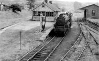 Black 5 45070 enters Garstang Town station on 13th August 1959 with a single brakevan. Taken nearly thirty years after passenger services finished, this photo clearly shows the very unusual signal box at Garstang, which was on the island platform but at right angles to the tracks. The signal box was wider than the main station building, although it shared the roof profile, allowing a view to the east for the signalman. <br><br>[Knott End Collection&nbsp;13/08/1959]