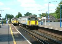 Trains passing over Lymington Road level crossing at the north end of Brockenhurst station in July 2002.<br><br>[Ian Dinmore&nbsp;26/07/2002]