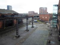 After fourteen years as a passenger station Liverpool Road was replaced by Manchester Victoria but continued in use as a Goods Depot until 1975. Many of the freight facilities can still be seen in its new role as part of the Museum of Science and Industry. This view taken from the main museum building in October 2017 shows the old sidings, the passenger station where the lines converge and the <I>Power Hall</I> on the left where the railway exhibits are housed. <br><br>[Mark Bartlett&nbsp;08/10/2017]