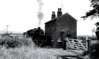 Black 5 45449 waits for the gates at Nateby Crossing Lane to be secured before continuing with a trip working to Pilling in the early 1960s. 1963 saw the closure of the line between Garstang Town and Pilling but the crossing cottage survives in 2017 [See image 18317] although its future is now less certain as the land between here and the A6 has been approved for housing development. <br><br>[Knott End Collection&nbsp;//]