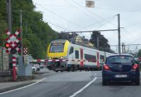 SNCB EMU 08099 rumbles over the level crossing in Dinant as it slows for the station with a service from Brussels Airport that has travelled down the scenic Meuse Valley from Namur. One last railway picture as we headed back to the UK. 10th September 2017 <br><br>[Mark Bartlett&nbsp;10/09/2017]