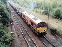 A trainload of coal empties on its way back to Ravenstruther restarts from a signal check at the north end of Millerhill Yard in June 2000. The locomotive is EWS 66051. <br><br>[John Furnevel&nbsp;05/06/2000]