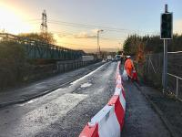 Preparations under way for the temporary reopening of the original bridge at Baillieston station. The bridge will close again in February for demolition and replacement.  The plastic barrier sections will require filling with water to ensure they don't find their way on to the track underneath as has happened recently.<br><br>[Colin McDonald&nbsp;16/11/2017]