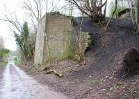 Remains of the northern abutment of the bridge that once carried the spoil tramway across the access road on its climb up to the tipping point on the south bing. The south portal of the sealed tramway tunnel is visible top right.<br><br>[John Furnevel&nbsp;10/04/2016]