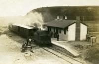 An interesting image of brand new (almost finished) Preesall station, on the 1908 extension of the line from Pilling to Knott End. 0-6-0T <I>Knott End</I> is pulling in with two of the Lancaster C&W veranda coaches and a guards van. Note the makeshift station sign in the foreground, presumably later replaced with a proper fitting. The station was only open for 22 years but after closure in 1930 goods trains continued to pass through until 1950.  <br><br>[Knott End Collection&nbsp;//1908]