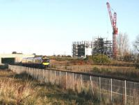 The Edinburgh and Midlothian Recycling and Energy Recovery Centre, under construction in the south west corner of Millerhill Yard, towers above the passing ScotRail 0911 Edinburgh - Tweedbank on 12 November 2017. The train is about to make its scheduled stop at Shawfair station, just off picture to the right.<br><br>[John Furnevel&nbsp;12/11/2017]