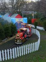 A steam-outline locomotive draws its train round the narrow gauge circuit of the Christmas Fair in Princes Street Gardens East on 28th November 2017.  Waverley Station is beyond the bushes in the distance.<br> <br> <br><br>[Bill Roberton&nbsp;28/11/2017]