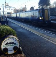 An electric train on the E&G passes a planter at Linlithgow station.<br><br>[John Yellowlees&nbsp;10/12/2017]