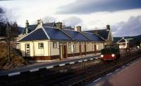 The main station building at Boat of Garten in late December 1975 with the 4w DM Motor Rail (ex Aberdeen Gas Works No.1D) sat in Platform 1. Reconstruction of the footbridge had just started as can be seen on the left with the appearance of the first 'tower'.<br><br>[John McIntyre&nbsp;30/12/1975]