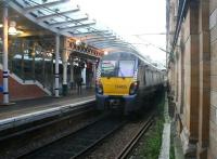 Unusual view looking west between the 'sub' platforms and the south wall at Waverley on 21 December 2017, showing ScotRail 334025 leaving platform 9 (W) with the 1107 service to Mingavie. Photographed through a glass panel at the base of the passenger access stairway serving platform 10. <br><br>[John Furnevel&nbsp;21/12/2017]