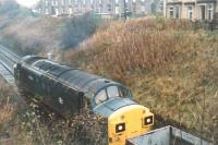 A class 37 shunts an engineering train out of the engineer's siding in Haltwhistle Station yard. Photograph taken from the old A69 overbridge looking west towards Carlisle in October 1989. [Ref query 17 January 2017] For a view of this loco looking across to the station area [see image 62576].<br><br>[Charlie Niven&nbsp;/10/1989]