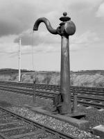 NER water column, located between the Down Main and Down Loop, to the north of Belford in 1987. An electrification mast in the background signals its demise, hopefully removed to a preservation site.<br> <br> <br><br>[Bill Roberton&nbsp;//1987]