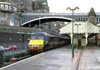 The recently arrived empty stock which will form the GNER 0900 service to Kings Cross stands at Waverley platform 21 early on a wet Sunday morning in September 2004. It would be another 8 years before work finally got underway on a replacement canopy for the 'sub' platforms [see image 43131]. <br><br>[John Furnevel&nbsp;05/09/2004]