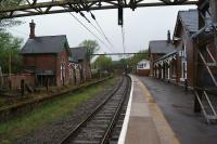 A view of the 'main line' platforms at Dinting looking east towards Hadfield on 12 May 2013. The electrification masts date from the 1500V DC era when this was the route between Manchester and Sheffield although the remaining sections to Hadfield and Glossop were converted to 25kV in 1984.<br><br>[John McIntyre&nbsp;12/05/2013]