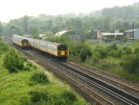 An approaching 12-car Brighton – London Bridge service passes a Horsham train on the Quarry Line just south of Stoats Nest Junction  in the Summer of 2002. The area on the right, consisting of wasteland and a scrapyard, had been occupied by Coulsdon North station and carriage sidings until closure in 1983 [see image 43249]. (Rail travellers continued to be well served by other nearby stations including Coulsdon Town and Coulsdon South). The location has since been redeveloped and the A23 Coulsdon relief road now runs through the site.<br><br>[Ian Dinmore&nbsp;18/06/2002]