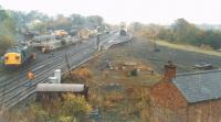 Lots of activity surrounding the arrival of an engineering train at Haltwhistle in October 1989. A Class 37 propels its wagons into a siding in the engineer's yard in the autumn mist. A tamper had already moved into another siding behind the platform.<br><br>[Charlie Niven&nbsp;/10/1989]