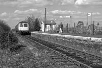 The country halt atmosphere at Bures on the Suffolk/Essex border is completed by the obligatory lady with a shopping bag. She has just alighted from the Cravens DMU on the departing service to Sudbury on 22nd March 1980, having probably spent the Saturday morning exploring the stores in Colchester. In 2017, the station became a 'request stop'.<br><br>[Mark Dufton&nbsp;22/03/1980]