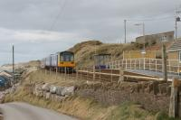 The tiny station at Braystones is in a remote but spectacular location on the Cumbrian Coast. Note the <I>Harrington Hump</I> and two sets of portable steps on the single platform as a southbound service hurries through on 8th March 2018. <br><br>[Mark Bartlett&nbsp;08/03/2018]