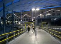 The ends of the old roof panels at Manchester Victoria have been replaced with strings of lights, which has the odd effect of making the station look a bit like a theatre at night. As the approaching Metrolink staff might respond with Northern humour, 'it's always a song and dance round here'.<br><br>[Ken Strachan&nbsp;18/07/2015]