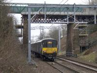 The 0817 to Whifflet passes under the Muirhead Road overbridge on 12th March 2018, the day after most of the bridge was expected to be removed during a line closure. More difficult to remove than anticipated, much of the bridge remains. <br><br>[Colin McDonald&nbsp;12/03/2018]